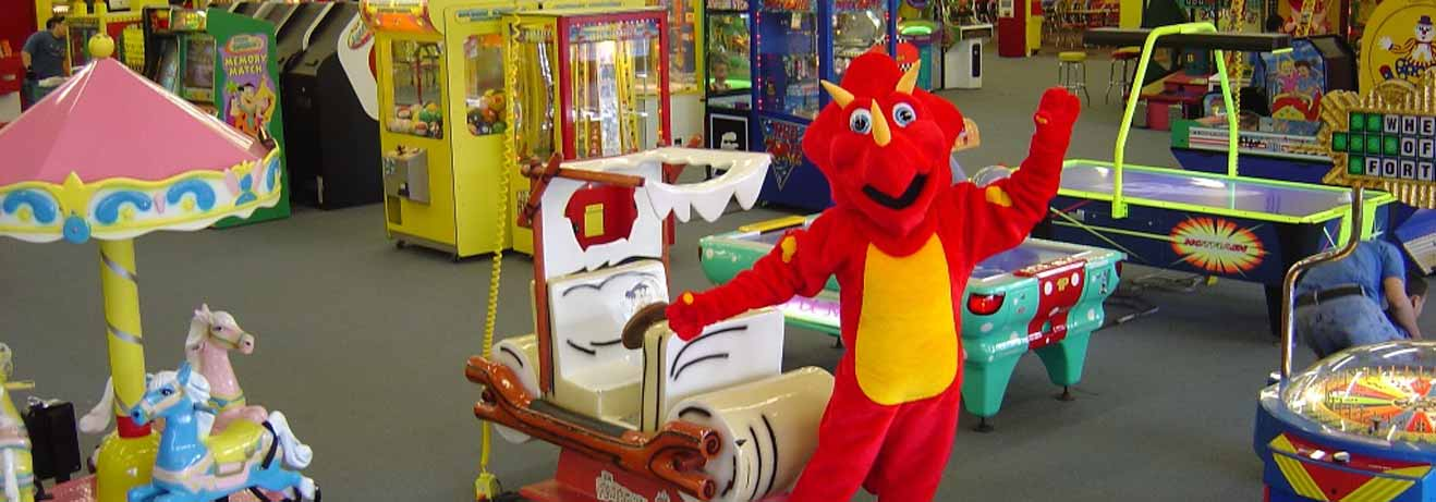 The People's Choice mascot posing in front of arcade games